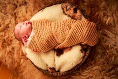 新出生的婴孩在圆的羊毛枕头睡觉 免版税库存图片