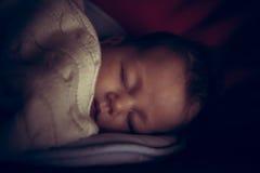 新出生的婴孩平安睡觉在有用舒适的毯子报道的低自然光的暗室象征和平 库存图片