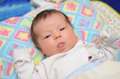 新出生的婴孩显示舌头 免版税库存照片
