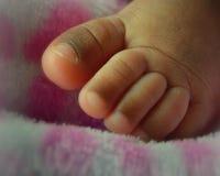 新出生的婴孩用脚尖踢非裔美国人 库存照片