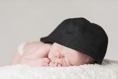 新出生的婴孩男性睡觉特写镜头佩带的帽子 免版税库存照片