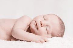 新出生的婴孩男性睡觉特写镜头面孔微笑 库存照片