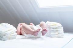 新出生的婴孩的脚在改变的桌上的与尿布 免版税图库摄影