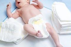 新出生的婴孩的脚在改变的桌上的与尿布 免版税库存照片