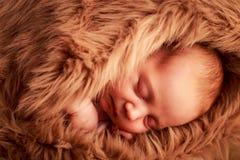 新出生的婴孩睡觉面孔特写镜头画象用在面颊下的手 免版税库存照片