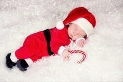 新出生的婴孩画象圣诞老人的给说谎穿衣在圣诞树下 库存图片