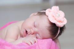 新出生睡觉在与被编织的花的篮子在头,女婴说谎在桃红色毯子的,逗人喜爱的孩子 库存照片