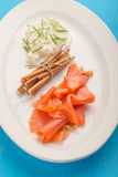 新切片在白色板材的熏制鲑鱼 库存图片