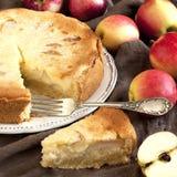 新切片苹果饼用整个饼在背景中 免版税库存图片