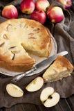 新切片苹果饼用整个饼在背景中 免版税库存照片