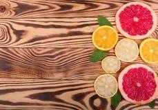 新切片水多的橙色,成熟柠檬和有机葡萄柚与薄菏在木背景,顶视图叶子  库存照片