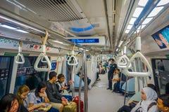 新加坡市,新加坡- 2013年11月13日:室内观点的路轨通勤者坐一列拥挤大量高速运输MRT火车 库存照片