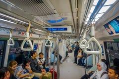 新加坡市,新加坡- 2013年11月13日:室内观点的路轨通勤者坐一列拥挤大量高速运输MRT火车 免版税图库摄影