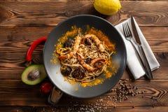 新加坡式面条用什塔克菇和虾在一个黑色的盘子在木背景 库存照片