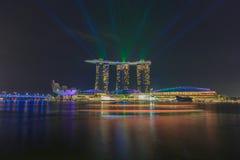 新加坡的Merlion在发出从小游艇船坞海湾的激光的雕象手表铺沙旅馆2016年5月15日 免版税图库摄影