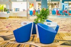 新加坡,新加坡- 2018年1月30日:等待的休息室区域室内看法与一个蓝色沙发的在樟宜里面 库存图片