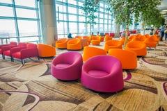 新加坡,新加坡- 2018年1月30日:等待的休息室区域室内看法与一些五颜六色的沙发的在樟宜里面 图库摄影