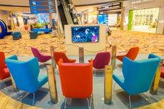 新加坡,新加坡- 2018年1月30日:等待的休息室区域室内看法与里面某一五颜六色的沙发和电视的  库存图片