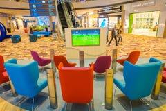 新加坡,新加坡- 2018年1月30日:等待的休息室区域室内看法与里面某一五颜六色的沙发和电视的  库存照片