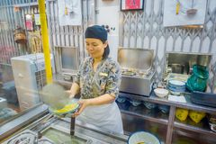 新加坡,新加坡- 1月30 2018年:供食在白色碗和新鲜的草本里面的未认出的妇女食物  库存图片