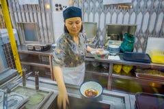 新加坡,新加坡- 1月30 2018年:供食在白色碗和新鲜的草本里面的未认出的妇女食物  免版税库存图片