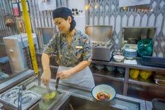 新加坡,新加坡- 1月30 2018年:供食在白色碗和新鲜的草本里面的未认出的妇女食物  库存照片
