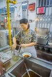 新加坡,新加坡- 1月30 2018年:的未认出的妇女为在白色碗里面的室内观点食物服务和 免版税库存图片