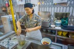 新加坡,新加坡- 1月30 2018年:的未认出的妇女为在白色碗里面的室内观点食物服务和 库存图片
