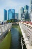 新加坡- 2016年4月30日:在小游艇船坞海湾的两座走的桥梁之间与在背景的高大厦 库存图片