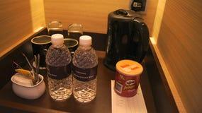 新加坡- 2015年4月2日:小型条信号角落在有水壶、玻璃、酒开启者和芯片的豪华旅馆室 免版税库存图片
