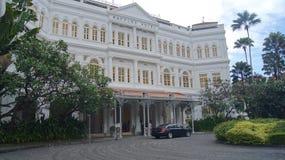 新加坡- 2015年4月2日:殖民地式莱佛士酒店的车道在新加坡 旅馆是一个最著名 免版税库存图片
