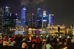 新加坡2018年10月-14:许多观众观看光和水展示,海的歌曲小游艇船坞海湾沙子前面的  免版税库存图片