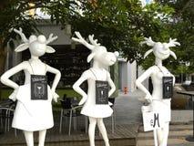 新加坡- 2009 6月1日,白色颜色穿着裙子的三头母大型装配架鹿艺术雕象  库存图片