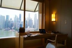 新加坡- 2016年7月23日, :有现代内部的豪华旅馆室和小游艇船坞海湾,运转的书桌的一个令人敬畏的看法 库存照片