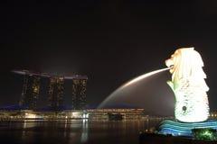 新加坡- 10月12日2015年:Merlion与小游艇船坞海湾的雕象地标在背景夜铺沙旅馆 免版税库存照片