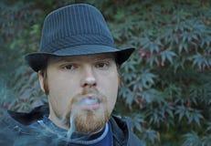 新吹的人的烟 免版税库存图片