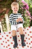新喝奶昔的男孩佩带的启动 免版税库存图片