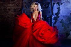 新壮观的妇女方式照片 跑往照相机 红色礼服的诱人的金发碧眼的女人有蓬松裙子的 免版税库存图片