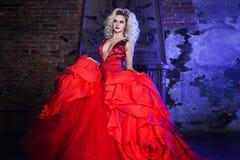 新壮观的妇女方式照片 跑往照相机 红色礼服的诱人的金发碧眼的女人有蓬松裙子的 免版税库存照片