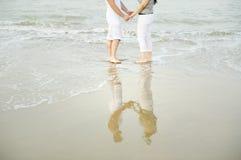 新夫妇在海滩的水中 库存照片