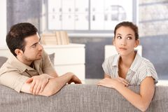 新夫妇坐在坏心情的沙发 免版税库存图片