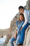 新夫妇坐岩石在海边。 免版税库存照片