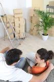 新夫妇坐沙发 免版税库存图片