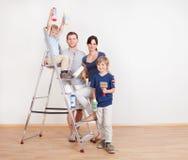 新夫妇绘画墙壁在家 免版税图库摄影
