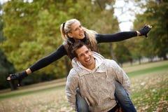 新夫妇获得乐趣在秋天公园 库存图片