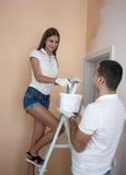 新夫妇绘画墙壁在家 免版税库存照片