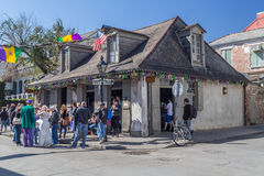 新奥尔良, LA/USA -大约2016年2月:人们和老房子在为狂欢节装饰的法国街区街道上 免版税库存照片