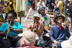 新奥尔良- 4月13 :在新奥尔良,爵士乐队演奏在街道的爵士乐曲调从游人的捐赠的 免版税库存照片