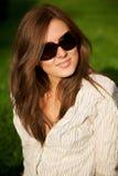 新女孩俏丽的微笑的太阳镜 免版税库存照片