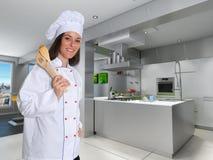 新女性主厨在一个现代厨房里 免版税库存照片